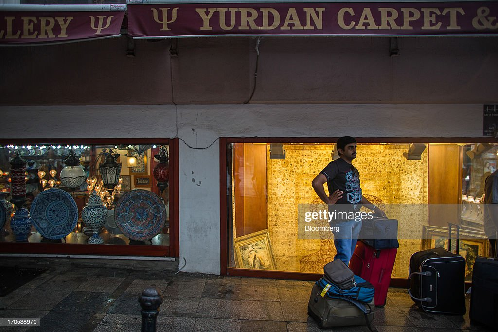 A tourist stands with his luggage outside souvenir and carpet stores in the Sultan Ahmed district of Istanbul, Turkey, on Friday, June 14, 2013. The law forbids the sale of alcohol at night and near schools and mosques, going against the secular traditions of the Muslim-majority country of 74 million, where many people drink and women often choose not to cover their hair. Photographer: Lam Yik Fei/Bloomberg via Getty Images