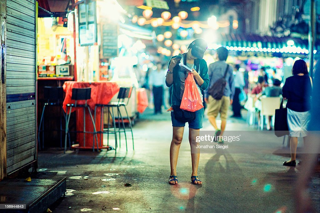 A tourist stops to check her guidebook while walking through Singapore's lantern lit Chinatown.