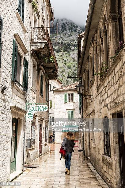 Tourist strolling in historic street in old town, Kotor, Montenegro