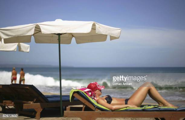 A tourist sunbathes on Kuta Beach on May 24 2005 in Bali Indonesia Australian travel agents have threatened to stop promoting Bali as a destination...