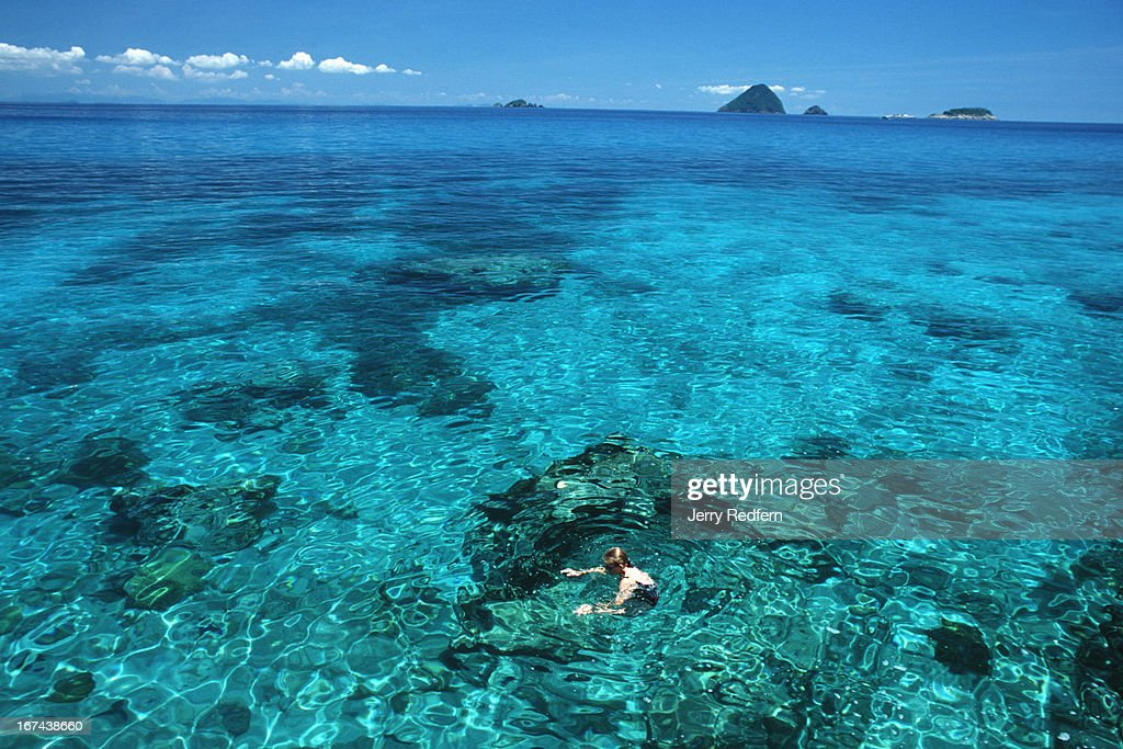 A tourist swims in the crystal-clear waters off the secluded north coast of Pulau Perhentian Kecil. Pulau Rawa are the islands in the distance..