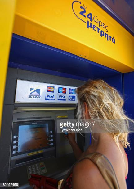 Tourist take out money from a cash machine in the village Lindos on August 08 2008 in Rhodes Greece Rhodes is the largest of the greek Dodecanes...