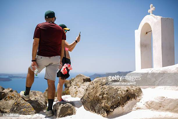 Tourist take photographs of a old Greec orthodox church next to the Aegon sea on June 11 2015 in Santorini Greece Santorini is an island in the...