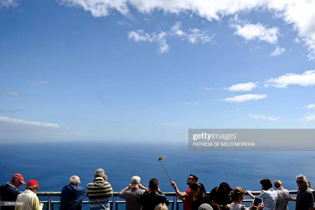 Tourist take pictures at Cabo Girao lookout in Camara de Lobos, on Madeira island on April 30, 2016. An 81 years old French tourist died today after falling into a 100 meters deep ravine while he was trekking on the hills of Camara de Lobos, in the Portuguese island of Madeira, firefighters said. / AFP / PATRICIA