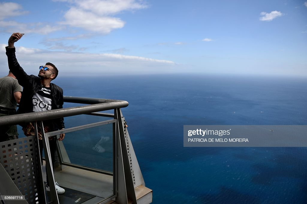 A tourist take pictures at Cabo Girao lookout in Camara de Lobos, on Madeira island on April 30, 2016. An 81 years old French tourist died today after falling into a 100 meters deep ravine while he was trekking on the hills of Camara de Lobos, in the Portuguese island of Madeira, firefighters said. / AFP / PATRICIA