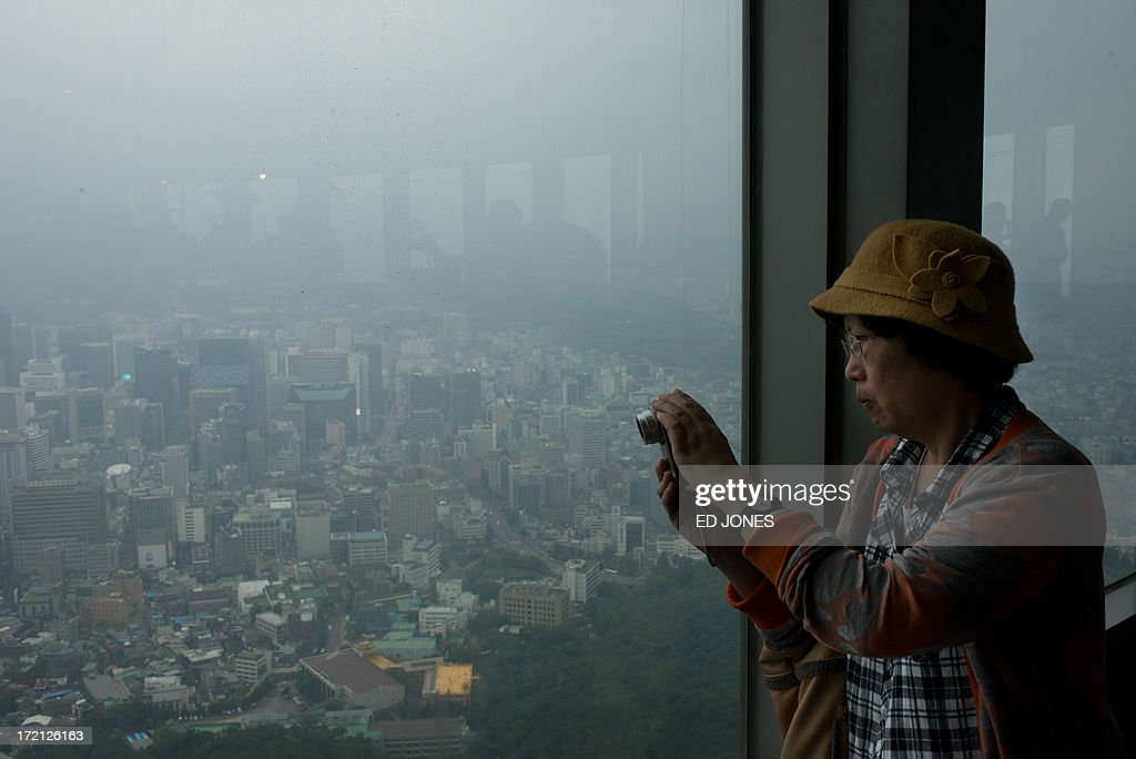 A tourist takes a photo from a window of the Namsan tower overlooking the Seoul city skyline during rainfall on July 2, 2013. July marks the wet season for Seoul during which the city of10 million people receives some 60 percent of its annual rainfall. AFP PHOTO / Ed Jones