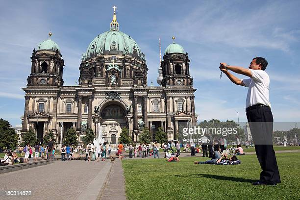 A tourist takes a photo in front of the Berliner Dom on August 15 2012 in Berlin Germany In 2010 nine million tourists visited the German capital and...