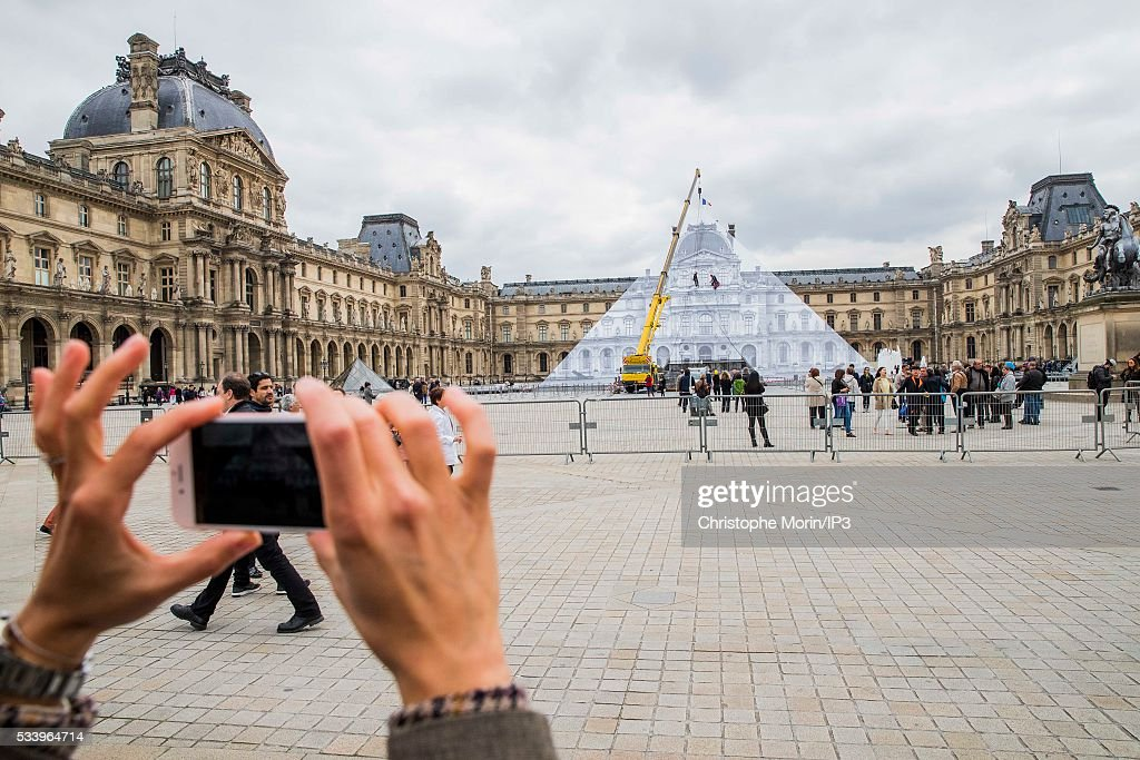 A tourist takes a photo of French street artist JR'd artwork outside The Louvre on May 24, 2016 in Paris, France. The artist has covered The Louvre Pyramid by an optical illusion made with black and white photos of 16th century buildings and is open to the public from May 25 to June 27, 2016.