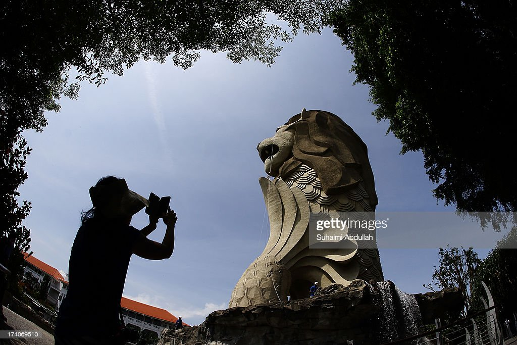 A tourist takes a photograph as people abseil at the Merlion at Sentosa during the OBS-The Merlion Charity Abseil on July 20, 2013 in Singapore. Abseiling The Merlion at Sentosa, an iconic national structure that stands at a formidable height of 37m, calls on donors to draw not just monetary contributions but also courage in literally stepping out of their comfort zone. All proceeds go to Life Community Services Society, a registered charity that takes care of disadvantaged children and at-risk youth from low income families and whose parents are incarcerated.