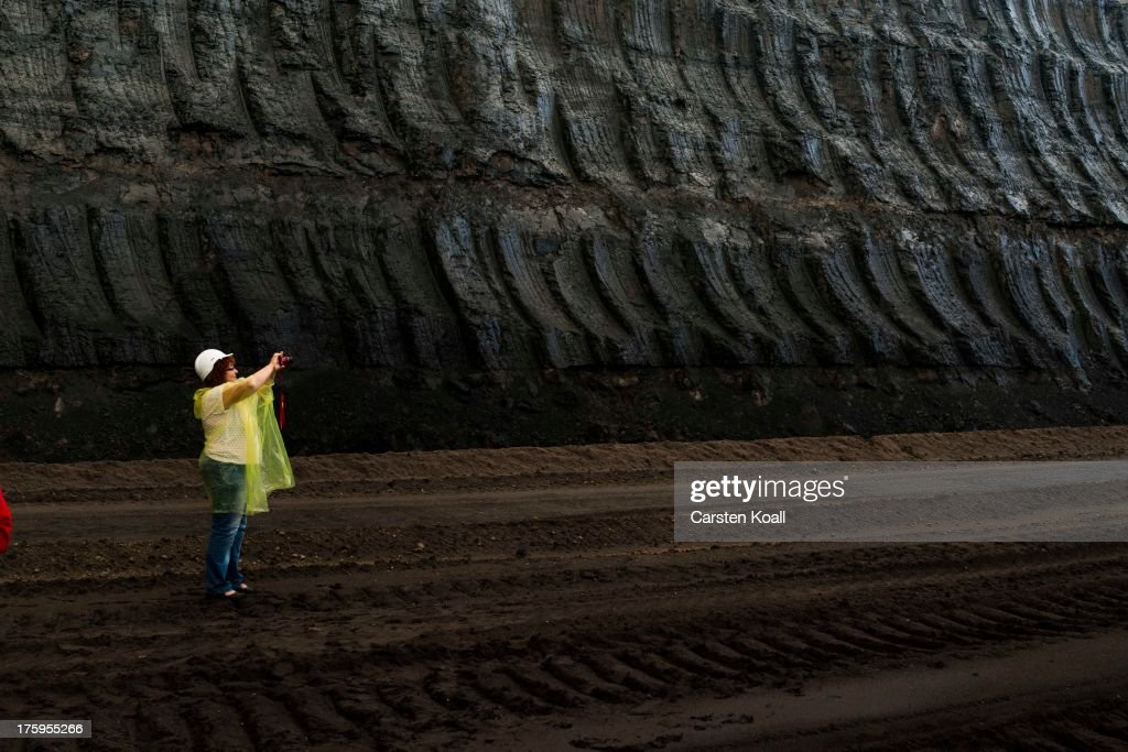 A tourist takes a photograph during a visit of a a brown coal opencast mine at dusk in the Welzow open-pit lignite coal mine on August 10, 2013 near Welzow, Germany. The mine, operated by Vattenfall, is one of several in the immediate area that feed a nearby power plant with coal. In a development project initiated by state government, other nearby former open-pit mines have been turned into lakes in a rejuvenation effort that is also intended to make the area a viable tourist destination.
