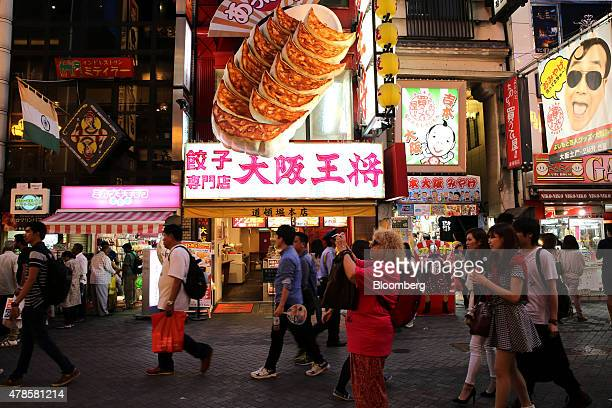 A tourist takes a photograph in the Dotonbori district of Osaka Japan on Wednesday June 24 2015Japanese consumer prices rose fractionally in May as...
