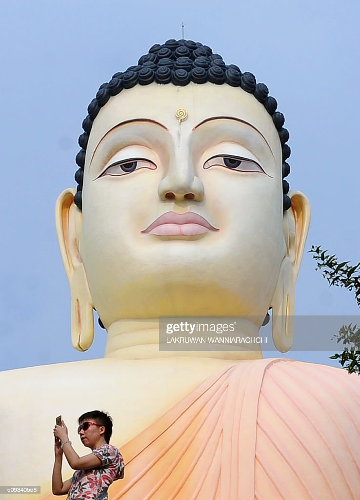 A tourist takes a photograph next to a statue of Buddha at the Kande Viharaya Temple in Aluthgama on February 10, 2016. AFP PHOTO / LAKRUWAN WANNIARACHCHI / AFP / LAKRUWAN WANNIARACHCHI