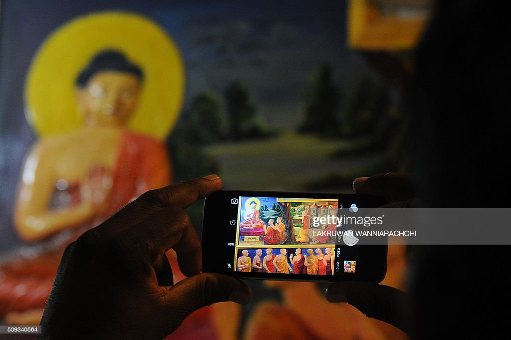 A tourist takes a photograph of a statue of Buddha at the Kande Viharaya Temple in Aluthgama on February 10, 2016. AFP PHOTO / LAKRUWAN WANNIARACHCHI / AFP / LAKRUWAN WANNIARACHCHI