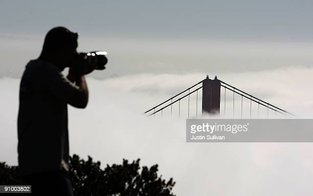 A tourist takes a photograph of the north tower of the Golden Gate Bridge as it peeks out from a blanket of fog September 21 2009 in the Marin...