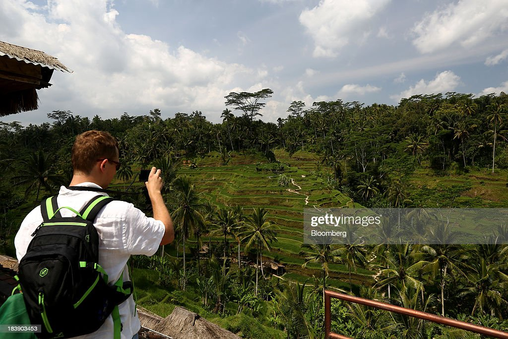 A tourist takes a photograph of the Tegallalang rice terraces in Ubud, Bali, Indonesia, on Tuesday, Oct. 8, 2013. Bank Indonesia said it will regulate currency hedging by individuals and companies, including state-owned firms, to help stabilize Asias most-volatile currency. Photographer: SeongJoon Cho/Bloomberg via Getty Images