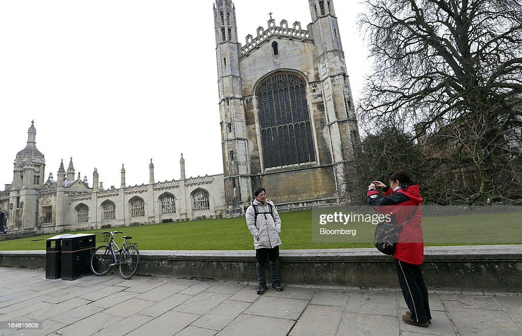 A tourist takes a photograph outside King's College chapel, part of the University of Cambridge, in Cambridge, U.K., on Friday, March 22, 2013. In 2011, the U.K.'s government unveiled a plan to reduce state spending on higher education and shift more of the costs to students through tuition increases and a loan program. Photographer: Chris Ratcliffe/Bloomberg via Getty Images