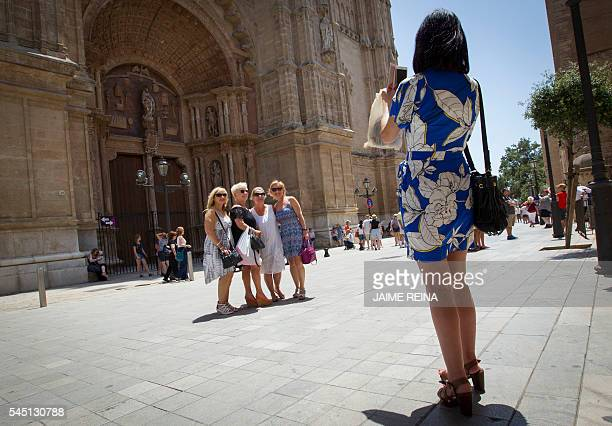 A tourist takes a picture at the entrance of the cathedral in Palma de Mallorca on June 30 2016 Spain is enjoying a surge in tourism in part as fears...