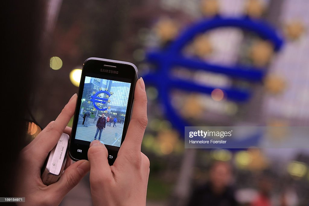 A tourist takes a picture from giant Euro symbol outside the headquarters of the European Central Bank (ECB) on January 8, 2013 in Frankfurt am Main, Germany. The governing board of the ECB is scheduled to meet this coming Thursday and analysts are predicting the bank will keep its interest rates steady.