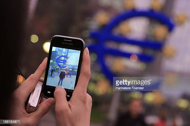 A tourist takes a picture from giant Euro symbol outside the headquarters of the European Central Bank on January 8 2013 in Frankfurt am Main Germany...