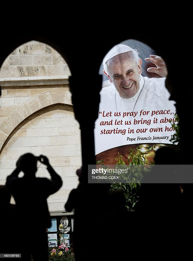 A tourist takes a picture of a banner bearing a portrait of Pope Francis displayed on the wall of the Saint Catherine Church inside the Church of Nativity in the West Bank town of Bethlehem, on May 20, 2014. Pope Francis will be treading on sensitive ground on an upcoming trip to the Middle East that is intended to promote inter-faith dialogue but has already sparked protests from ultra-orthodox Jews and radical Islamists. AFP PHOTO / THOMAS COEX
