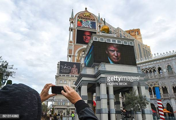 A tourist takes a picture of a display advertising the upcoming Republican presidential debate hosted by CNN December 14 2015 on the strip in Las...