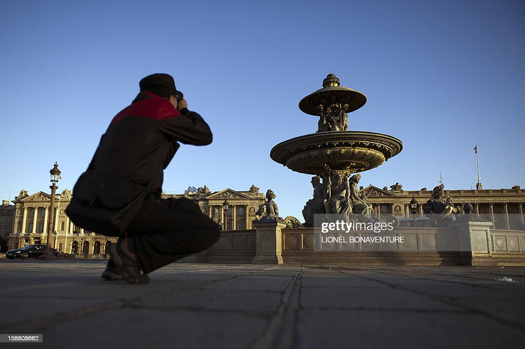A tourist takes a picture of a fountain at sunrise at the Concorde square in Paris on December 30, 2012.