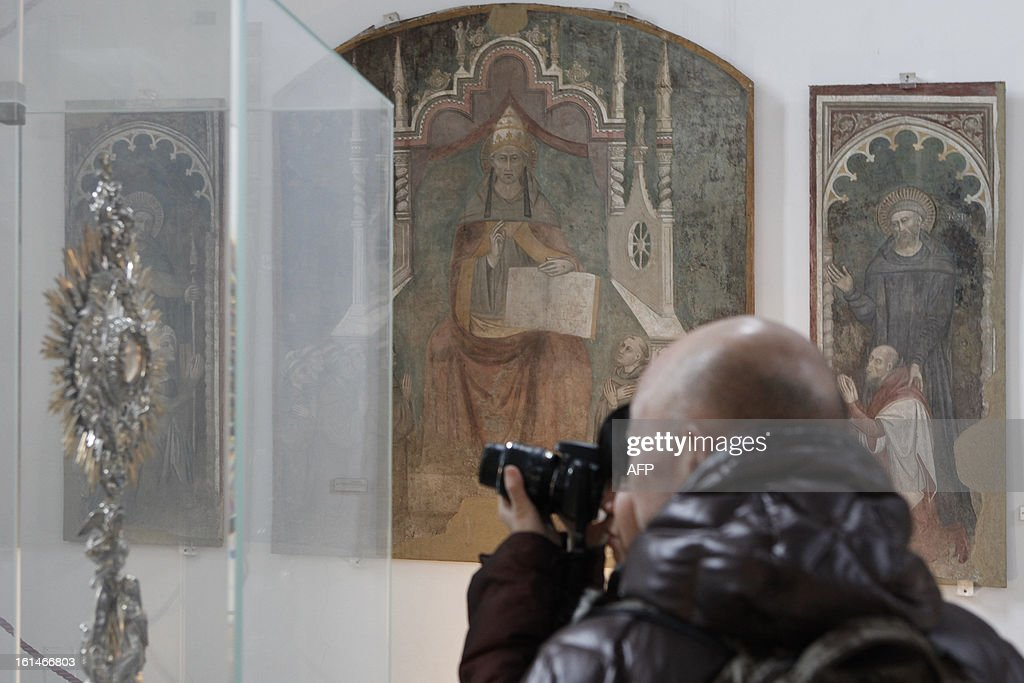 A tourist takes a picture of a painting showing Pope Celestine V by Italian painter Niccolo' Di Tommaso (Florence, Italy 1346-1376) in the museum of CatelNuovo in Naples on February 11, 2013. Pope Benedict XVI announced on February 11, 2013 his resignation, while the last pope to have abdicated the papacy is Celestine V in 1294.