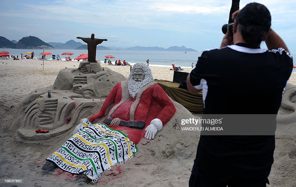 A tourist takes a picture of a sand sculpture depicting Santa Claus at Copacabana beach in Rio de Janeirro, Brazil on December 12, 2012. High temperatures -35 to 38 degrees celcius- during the end of the spring, have taken citizens and tourists to the beaches of Rio de Janeiro.