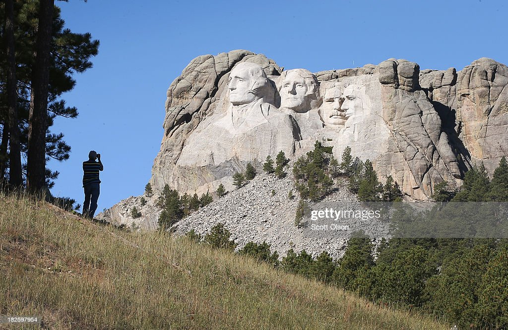 A tourist takes a picture of Mount Rushmore National Memorial from outside the park on October 1 2013 in Keystone South Dakota Mount Rushmore and all...