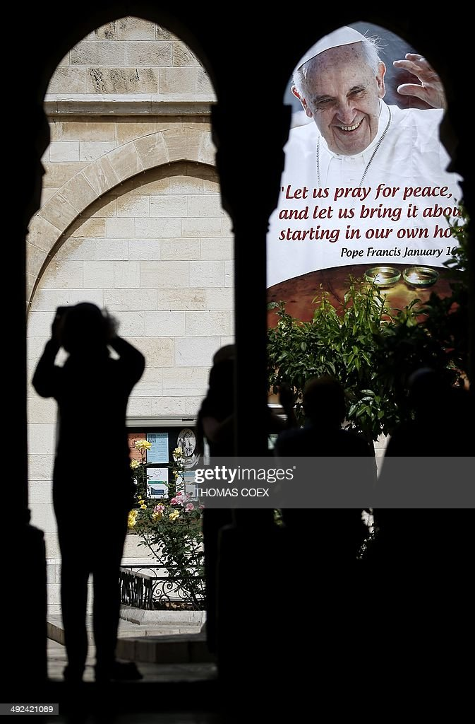 A tourist takes a picture of the banner bearing a portrait of Pope Francis displayed on the wall of the Saint Catherine Church inside the Church of Nativity in the West Bank town of Bethlehem, on May 20, 2014. Pope Francis will be treading on sensitive ground on an upcoming trip to the Middle East that is intended to promote inter-faith dialogue but has already sparked protests from ultra-orthodox Jews and radical Islamists.