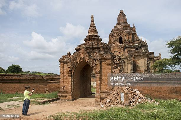 A tourist takes a picture of the damaged ancient Tayoke Pyay Temple on August 26 after a 68 magnitude earthquake hit Bagan A powerful 68 magnitude...