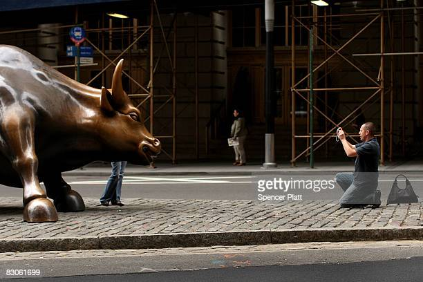 A tourist takes a picture of the Wall st bull in the financial district September 30 2008 in New York City Yesterday the Dow fell over 777 points or...
