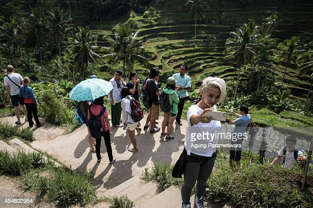 Tourist takes a self picture use smartphone with a backgroud of scenery Tegalalang rice terrace on September 4 2014 in Gianyar Bali Indonesia...