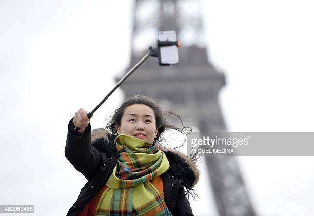 A tourist takes a 'selfie' at the 'Esplanade du Trocadero' in front of the Eiffel Tower on February 8 2015 in Paris AFP PHOTO/MIGUEL MEDINA