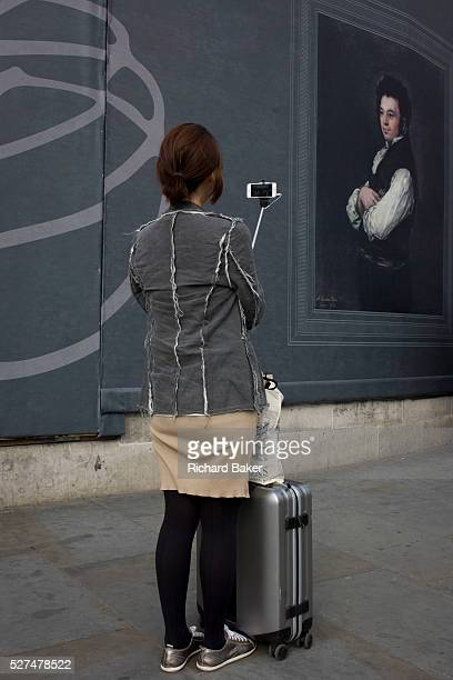 A tourist takes a selfie near a Francesco Goya portrait of Don Tiburcio P��rez y Cuervo the Architect sponsored by Credit Suisse and advertised on a...