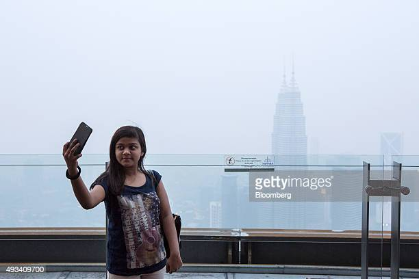 A tourist takes a selfie photograph as the Petronas Twin Towers stand shrouded in haze in Kuala Lumpur Malaysia on Monday Oct 19 2015 The choking...