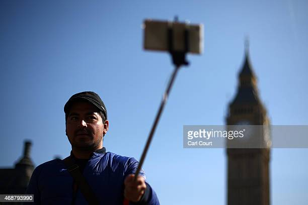 A tourist takes a selfie photograph in front of Big Ben using a selfie stick in on April 7 2015 in London England Parts of Britain basked in sunshine...