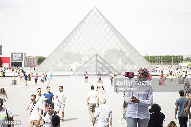 A tourist takes a selfie using a selfie stick in front of the Louvre Pyramid on August 6 2015 in Paris France Using a selfie stick has become a more...