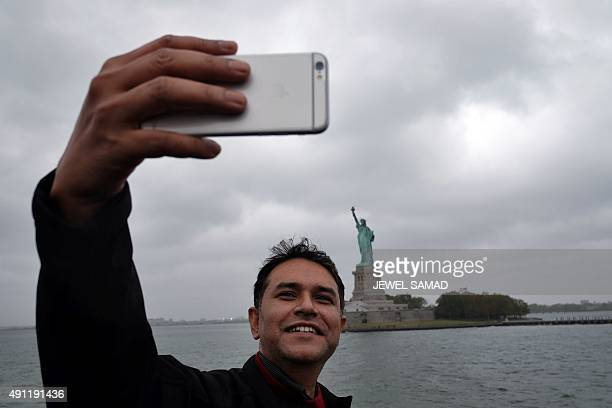 A tourist takes a selfie with the Statue of Liberty as cloud hover over it in New York on October 3 2015 AFP PHOTO/JEWEL SAMAD