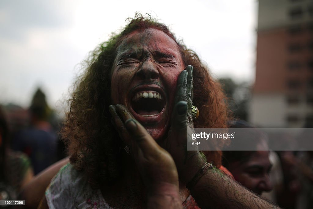 A tourist takes part in the celebration of 'Holi' with coloured powders at a temple in Kuala Lumpur on March 31, 2013. Holi, the festival of colours where people smear each other with coloured powder and water, is celebrated by Hindus across the country. AFP PHOTO / MOHD RASFAN