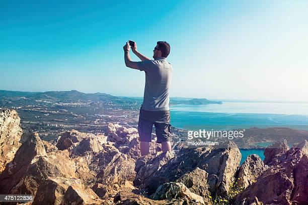 Turista prende foto mentre in piedi su un punto di vista sulle montagne