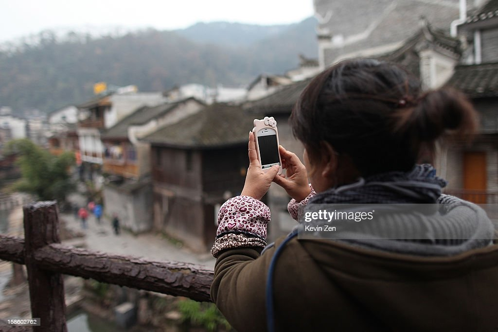 A tourist takes photo with iphone on December 18, 2012 in Fenghuang, China. Fenghuang Town was built by Emperor Kangxi in 1704 and after 300 years, the city's ancient appearance has been well preserved. Hunan is located in southwest Hunan Provience of China with a population of 370,000 within a total area of 1700 square kilometers.