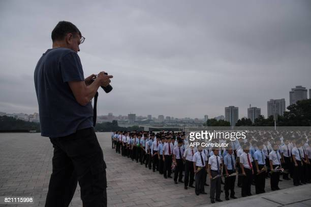 A tourist takes photos before a group of people gathered to pay their respects before statues of late North Korean leaders Kim IlSung and Kim JongIl...