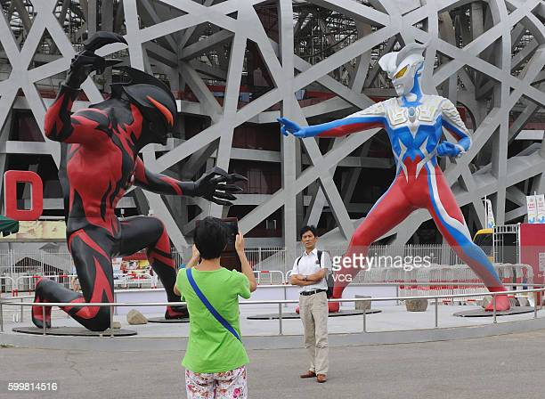 A tourist takes photos of sculptures of a 5metertall superhero 'Ultraman' and a monster Belial beside the National Stadium on September 6 2016 in...