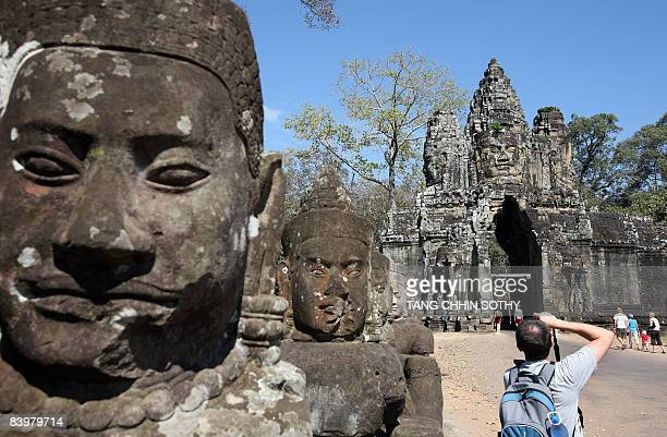 A tourist takes picture at the gate of the Angkor Thom temple in Siem Reap province some 314 kilometers northwest of Phnom Penh on December 7 2008...