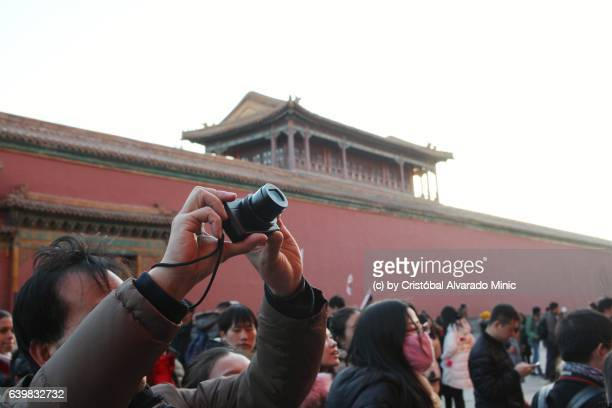 Tourist takes picture in Forbidden City, China.