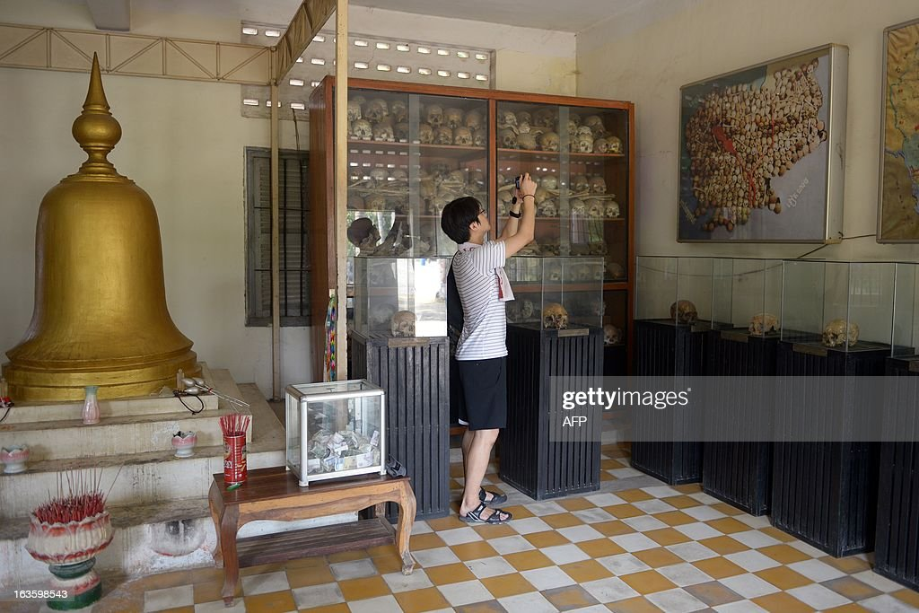 A tourist takes picture near skulls at the Tuol Sleng genocide museum in Phnom Penh on March 13, 2013. A former Khmer Rouge leader on trial for genocide is in critical condition in hospital, his lawyer said on March 6, stoking fears that top figures in the murderous regime may never face justice.
