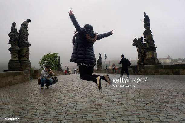 A tourist takes picture of his girlfriend jumping at the Charles Bridge on May 31 2013 in Prague AFP PHOTO/MICHAL CIZEK