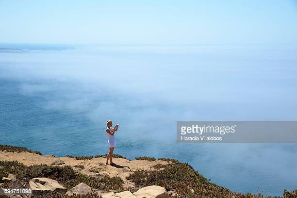 A tourist takes pictures above low clouds by the cliff on August 22 2016 in Cabo da Roca Sintra Portugal Cabo da Roca is a cape which forms the...