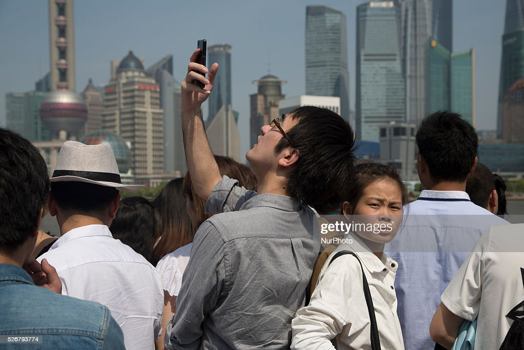 Tourist takes pictures by the Bund during the Labour Day holidays in Shanghai on May 1 2016.